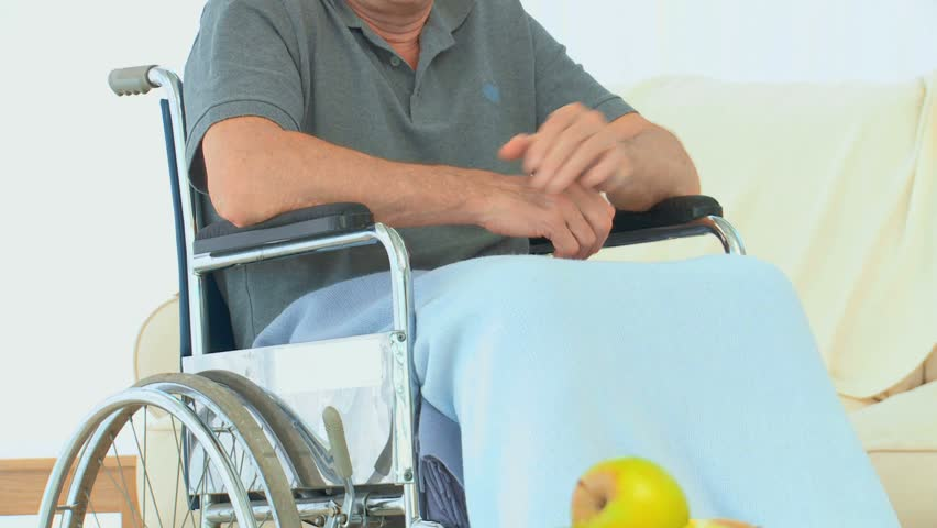 Man in a wheelchair looking at the camera in the living room   Shutterstock HD Video #1117732