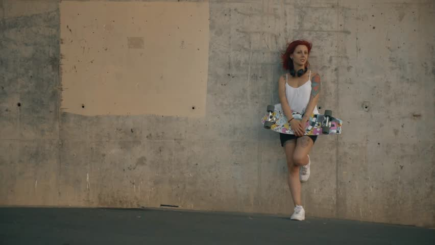 Tattooed red head woman stands in a concrete wall with his skateboard