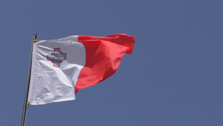 Close up of white and red with St George cross national flag of Malta isolated against blue sky waving in a wind on flagpole