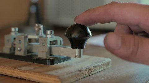 Morse code transmitter sending a message. Finger clicking on the knob of morse code transmitter. World war two looking transmitter.