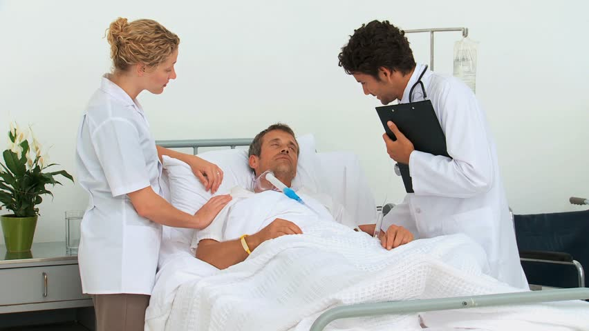 Two Doctors Visiting An Unconscious Patient At The