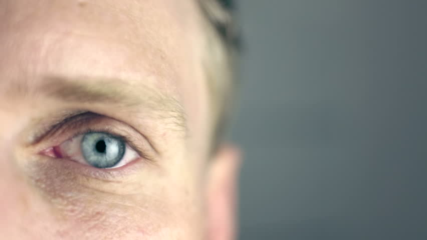 42e9f4a0c43 Blue eye blinking (slow motion) Young european man in a tired but relaxed  mood blinking with his blue eyes in dark surrounding.