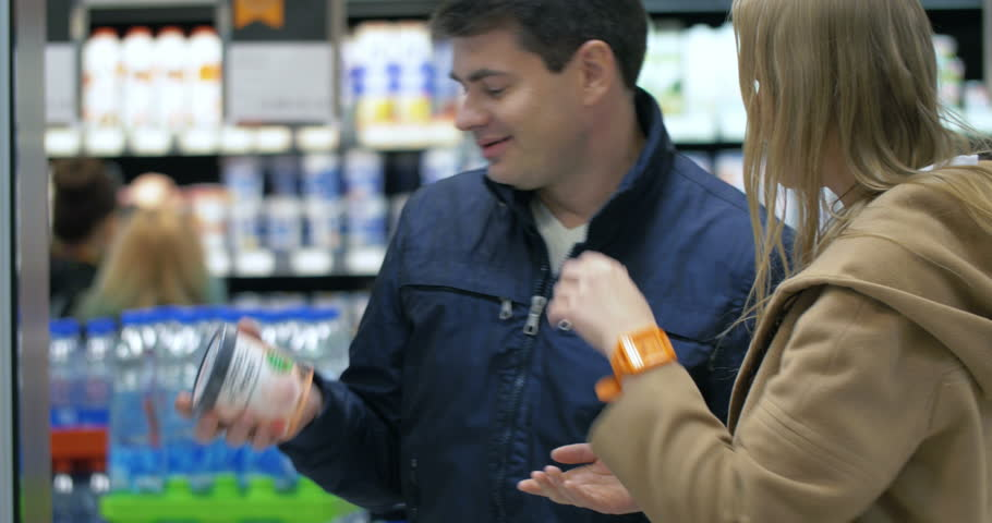 Young couple shopping in the supermarket. Man taking ice-cream from the fridge, but woman is angry with him. He putting it back, but returning alone and taking it again