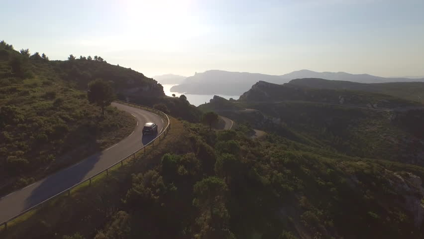 AERIAL: Flying above SUV jeep driving over mountain pass road towards the beautiful sunny ocean | Shutterstock HD Video #11245688