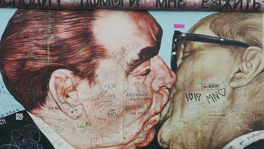 BERLIN, GERMANY - JULY 2015: Famous male kiss of Brezhnev and Honecker at the Berlin Wall. Zoom out shot