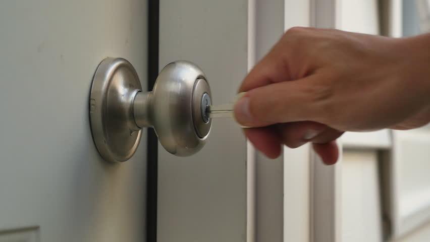 A man unlocks a house's door and enters. | Shutterstock HD Video #11288984