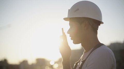 Engineer builder using a walkie talkie giving instructions at a construction site. Sunset time. Slow motion