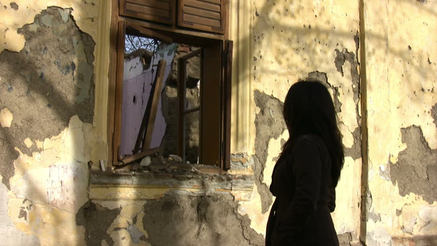 Young woman looking to old ruined house