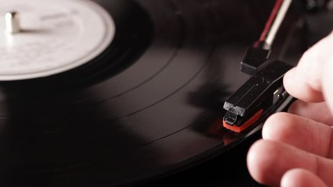 Close up macro of a record being played on a retro turntable that plays vinyl vintage records. Record players and turntables were popular in the 50s, 60s, and 70s and are now used by DJs.