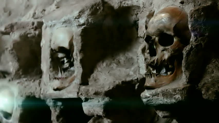 Wall of human skulls ;Human skull built into the stone wall,  video clip with light effects