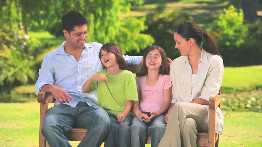 Family Sitting On A Park Bench While Talking To Each Other
