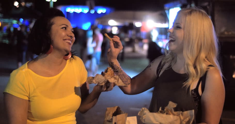 4K A hip trendy woman jokes around and offers friend a bite of her delicious street food truck french fries in a urban outdoor music festival night setting. | Shutterstock HD Video #11372936