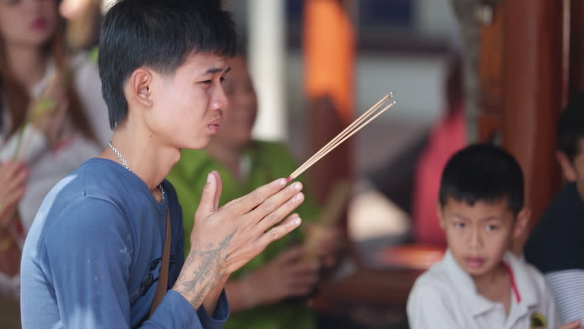 Phitsanulok, Thailand - February 7, 2015: An unidentified Buddhist boy prays with incense sticks in his hands at the temple in Phitsanulok in Central Thailand on February 7, 2015.  | Shutterstock HD Video #11404292