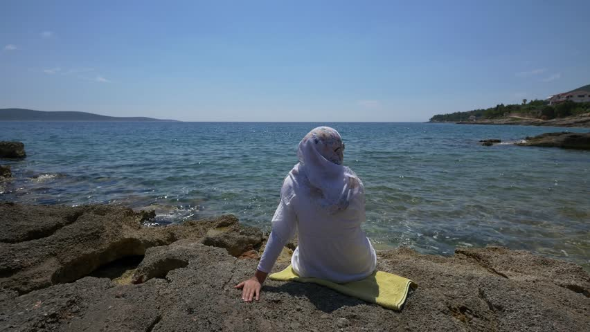 HVAR - JUNE 06, 2015: Lonely muslim woman sitting on the beach on Hvar island and enjoying the view on the ocean horizon. 4K footage June 06, 2015 in Hvar, Croatia.  | Shutterstock HD Video #11457713