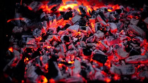 Close view at a glowing charcoal and flame in the barbecue grill. Shallow depth of field.