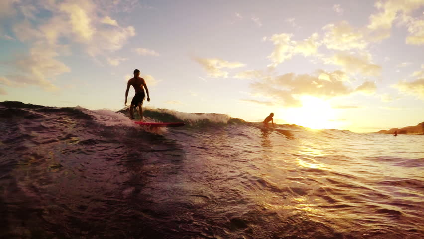 Young Man Surfing a Longboard Down The Line Away From the Camera Through a Golden Sunset in Hawaii in Slow Motion. POV Point of View