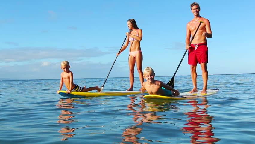 Family Stand Up Paddling at Sunrise. Summer Fun Family Vacation Healthy Lifestyle. Learning to Surf. SUP.