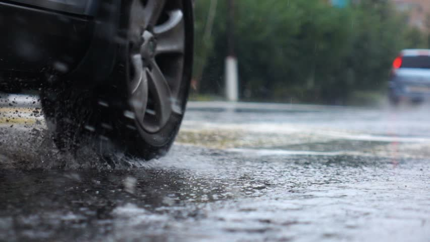 Rainy day in city streets, water drops, puddles, streams, ripple, car passing by, slow motion, selective focus, close up. #11554832
