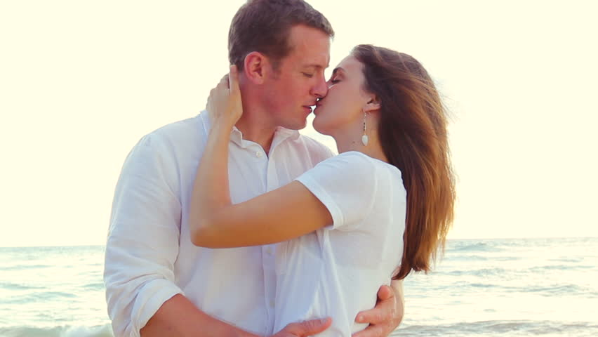 Attractive Young couple holding each other and kissing. Romantic Newlywed happy young couple enjoying ocean sunset during travel holidays vacation getaway. Shot with Steadicam.