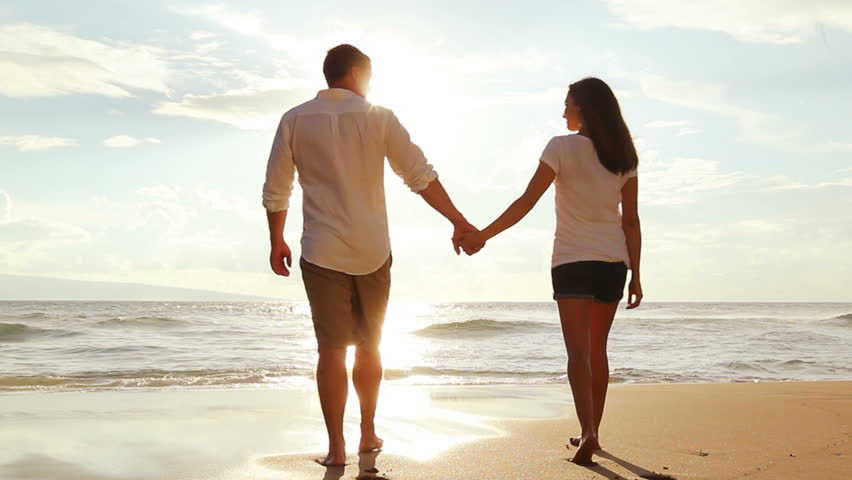 Honeymoon passionate couple holding hands walking down the beach. Sun Flares. Romantic Newlywed happy young couple enjoying ocean sunset during travel vacation getaway freedom joy. Steadicam.