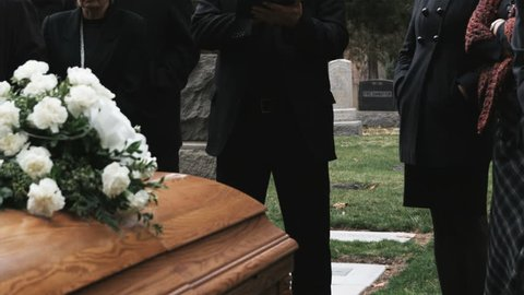 priest giving a eulogy at a funeral