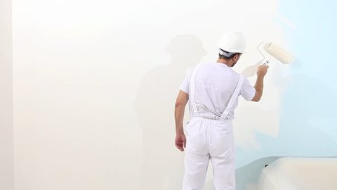 painter man at work, with roller painting the wall, painter house concept