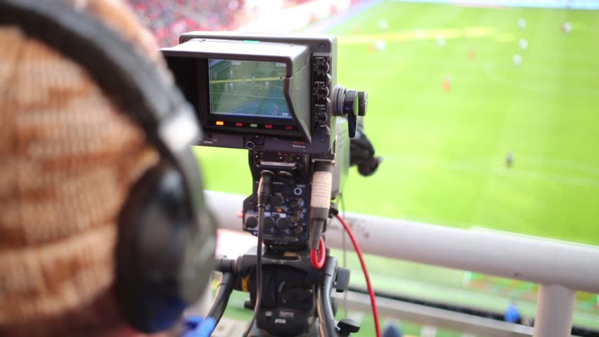 Cameraman shoots video reportage at stadium during game between soccer teams.