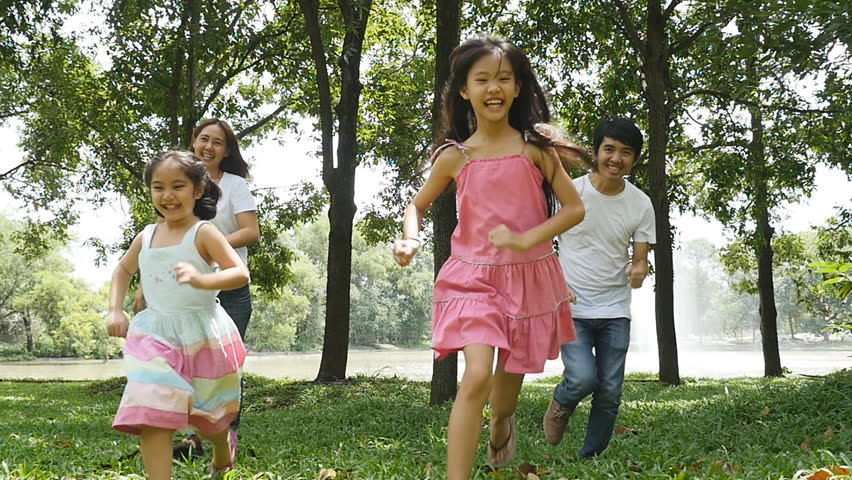 Asian family running together in the park