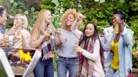 4K Happy mixed ethnicity group of friends dancing & drinking beer at bbq. Shot on RED Epic.