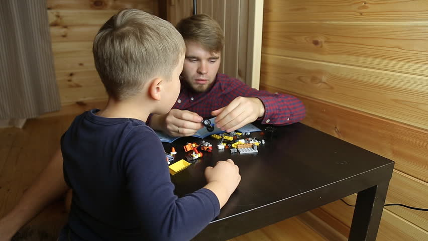 Father and son playing with lego cubes