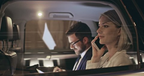 Businesswoman making phone call while her colleague using tablet computer in back seat of moving car