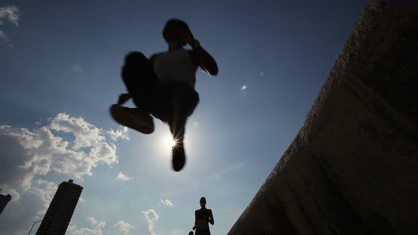 Silhouette of group of young people running and jumping in Havana, Cuba. Low angle view