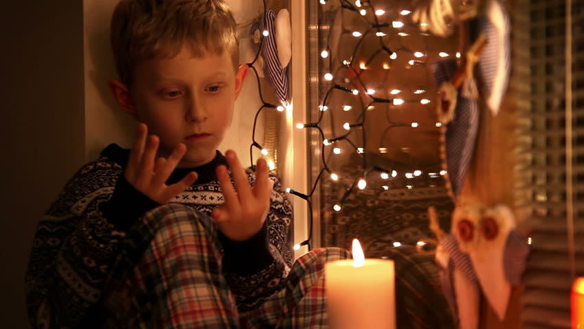 Cute little boy sitting on the windowsill counting days remaining till Christmas