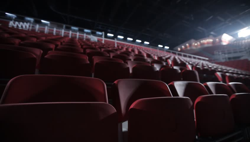 Camera dollies out to reveal empty seats in a basketball arena