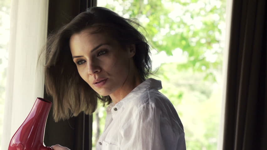 Beautiful woman drying hair standing near a window, shot at 240fps