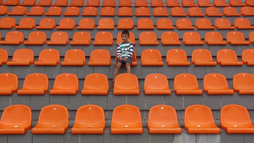 boy sitting at the stadium and glad his team scored a goal. happy boy watching match at stadium, boy shows emotion, the boy sits alone in the stadium hockey, ice hockey, soccer, basketball, volleyball | Shutterstock Video #11787284