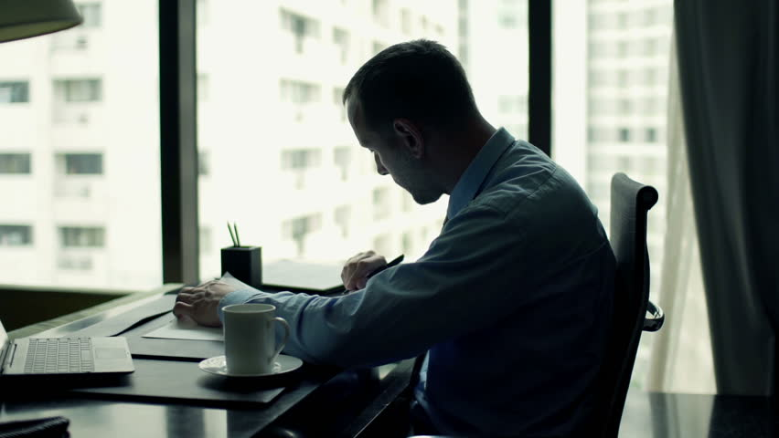 Businessman writing notes in documents sitting by table at the office  | Shutterstock HD Video #11807072