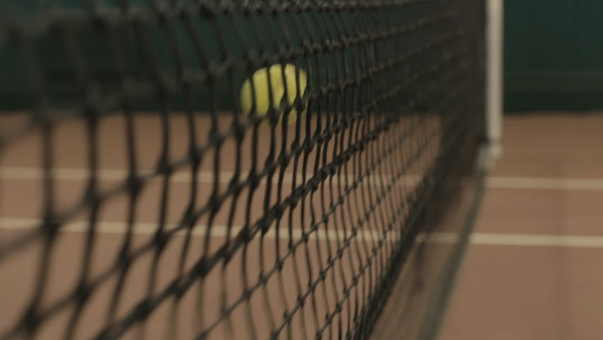 Yellow-green tennis ball stuck in the grid on red clay courts. Small depth of field