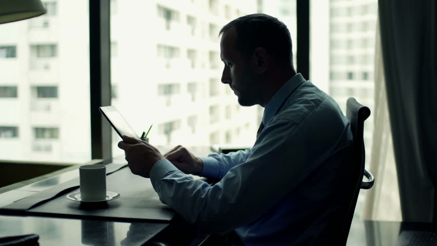 Happy, successful businessman with tablet computer sitting by desk at office  | Shutterstock HD Video #11813312