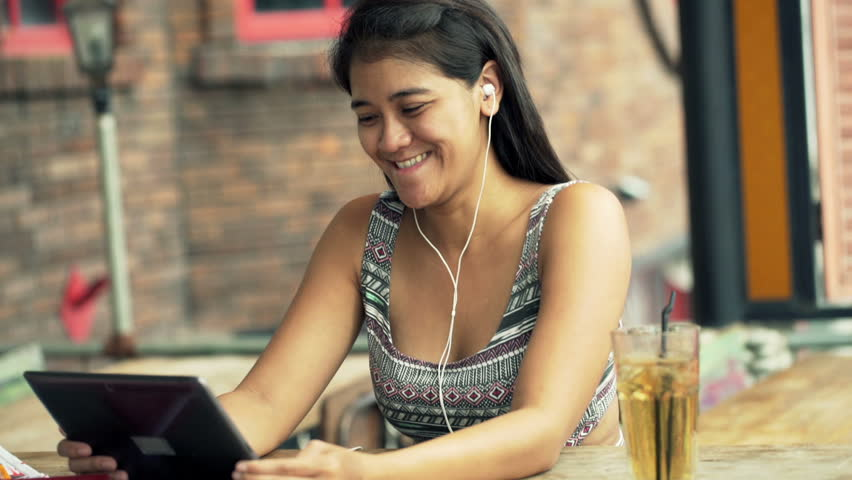 Happy, young woman watching movie on tablet computer sitting in cafe