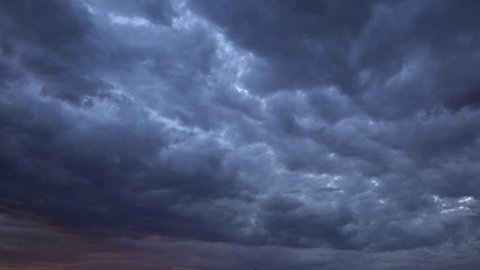 Time Lapse, Dark rumbling storm clouds spread across sky, morphing to deep red as edge of sunset emerges. 4K UHD 3840x2160