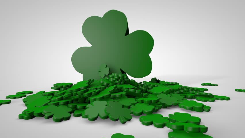 Shamrocks Falling on White. A single small shamrock falls and is followed by many more. A large shamrock falls on to the pile at the end. Luma matte to isolate smaller shamrocks