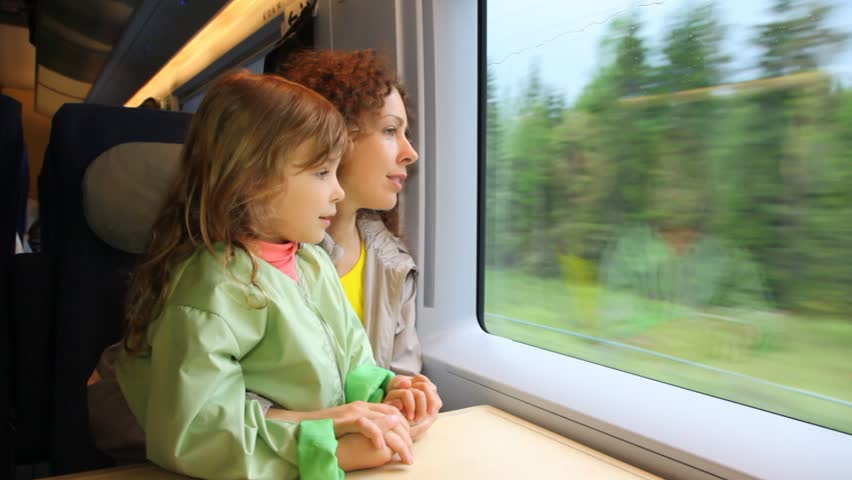 mother with daughter ride in speeding train and look at window