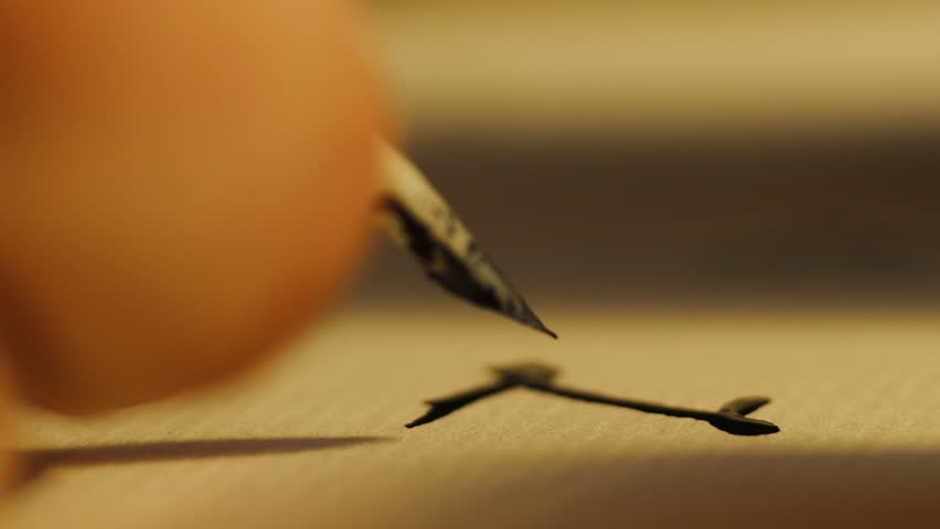 Close up shot of man writing with quill pen