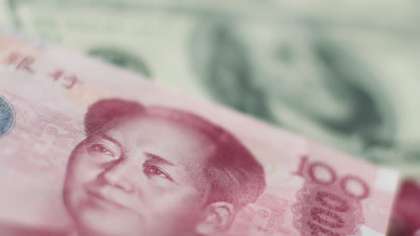 Rack focus from Chinese 100 Yuan note to 100 US dollar bill and back
