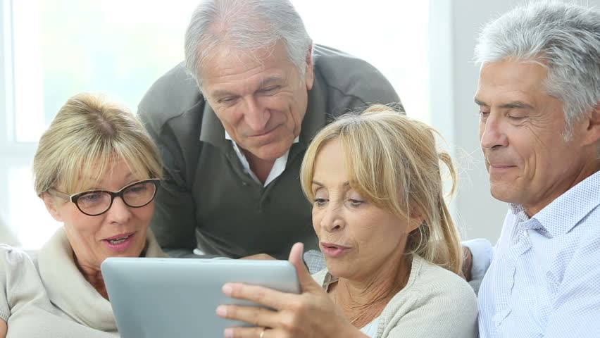 Group of retired people sitting in sofa and using tablet