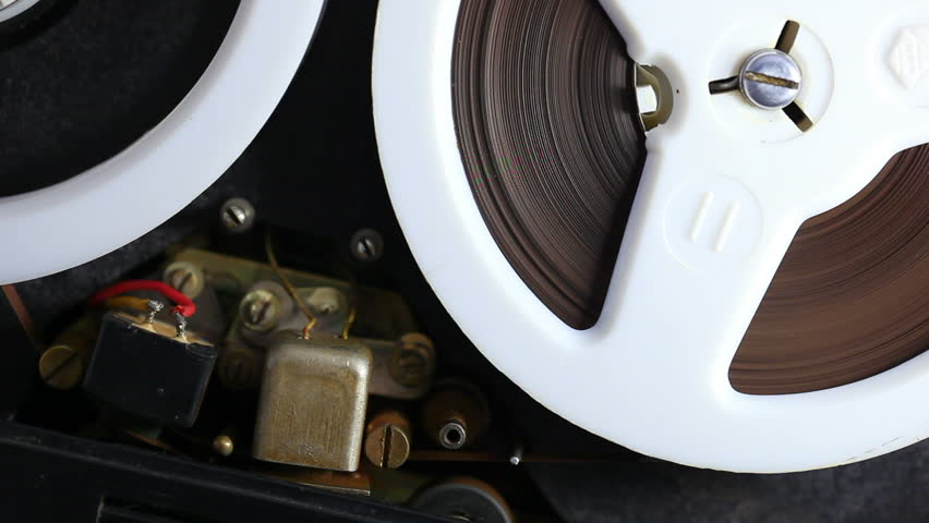 Open reel audio tape recorder reels spinning. Close-up.