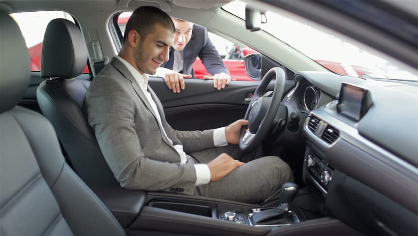 Man at a car dealership buying an auto. Auto business, car sale, technology and people concept - happy male with car dealer in auto show or salon. Young man with a salesman in a motor show. | Shutterstock HD Video #11918789