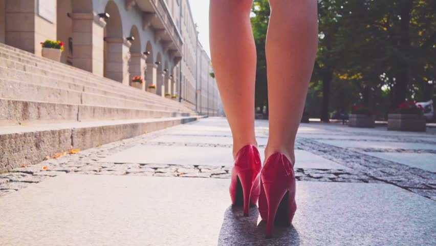 29f7d5295dd Sexy woman legs in red high heels shoes walking in the city urban street.  Steadicam stabilized shot in Slow motion. Lens flare. Businesswoman Female  legs in ...