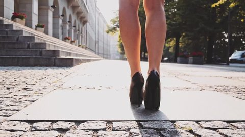Sexy woman in black high-heeled shoes walking in the city urban street then climbs the stairs, close up on feet. Steadicam stabilized shot in Slow motion. Business woman in the morning. Lens flare.
